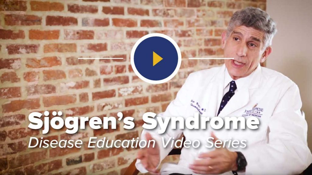 Dr. Alan Baer in Chair in Front of Brick Wall Discussing Sjögren's Syndrome